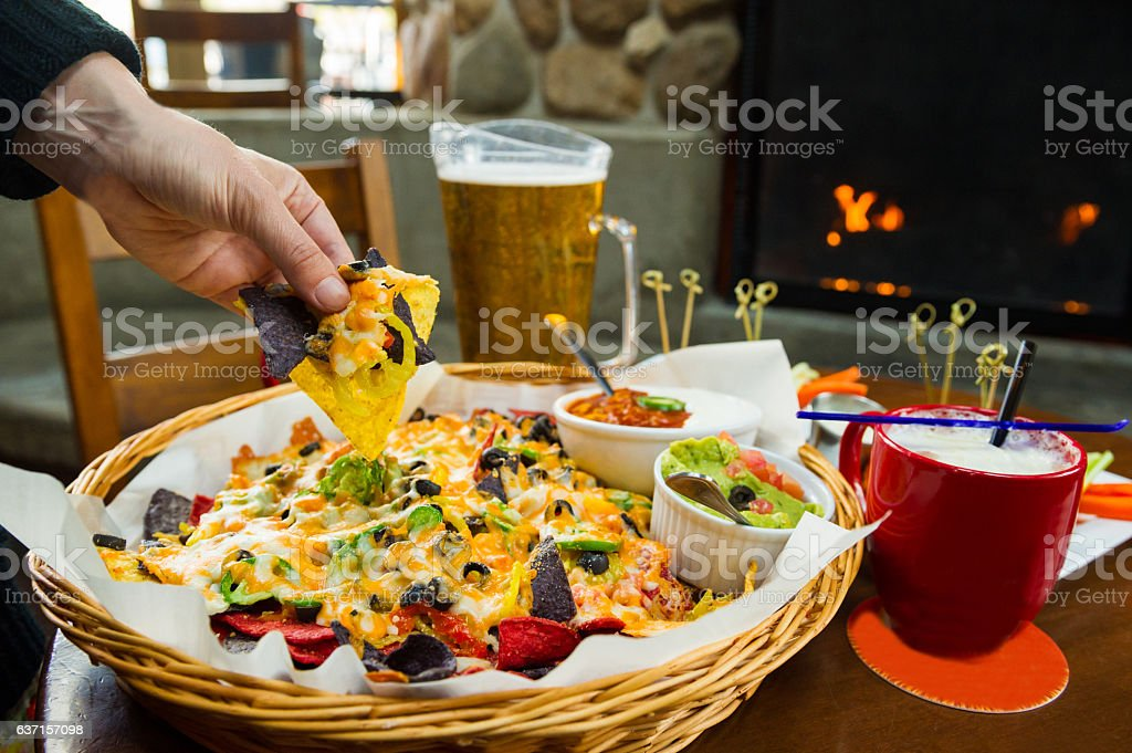 Nachos and beer by the fire stock photo
