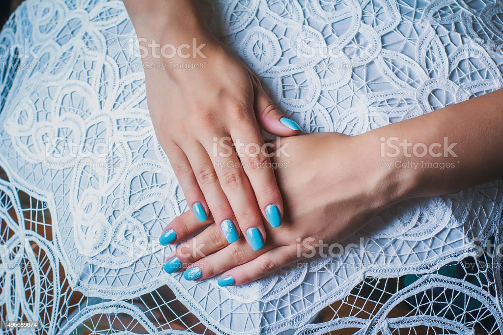 Nail art with blue background and white lace stock photo