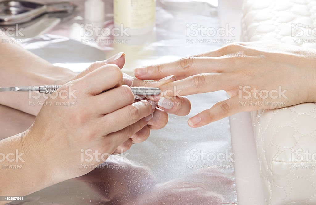 Removing cuticles with metal pusher.