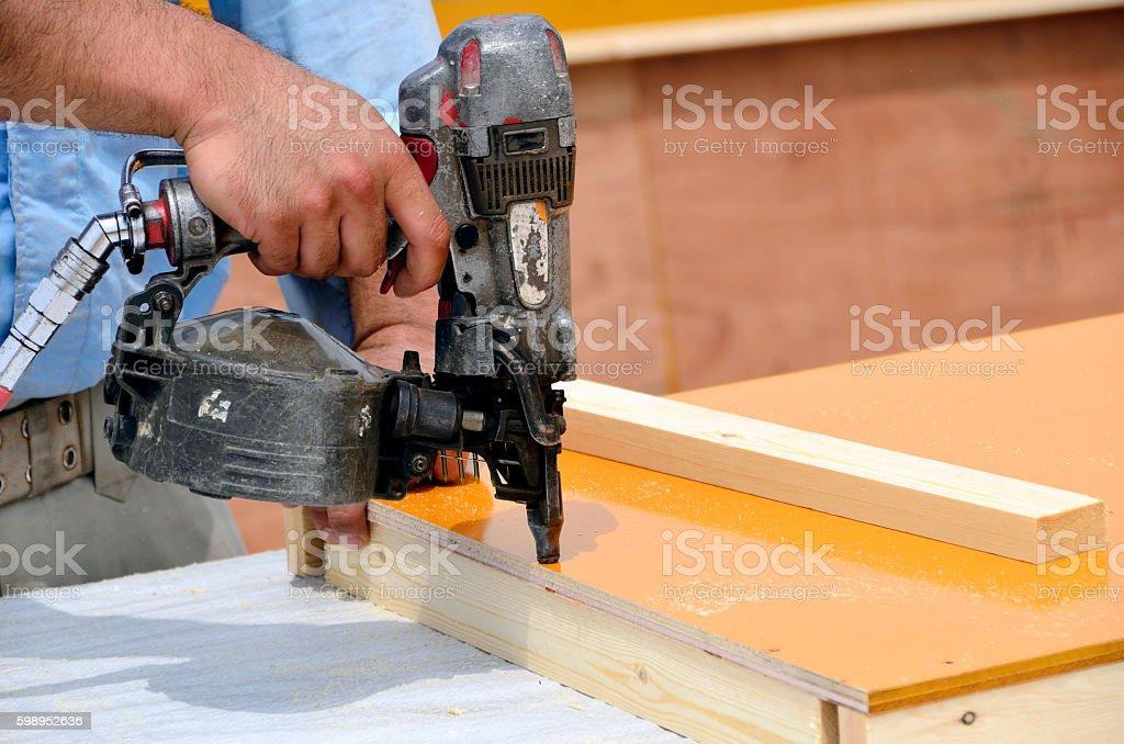 Nail gun and the formwork panel stock photo