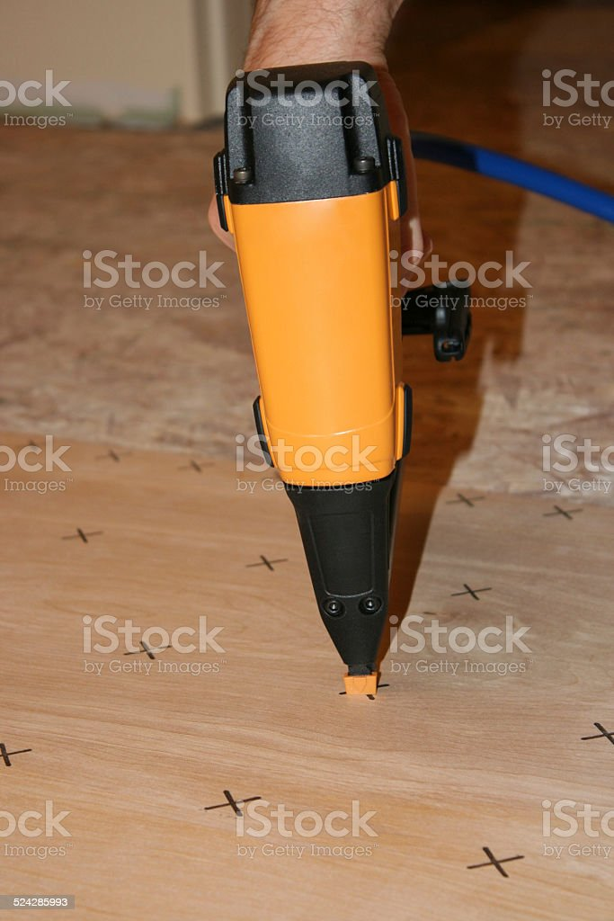Nail Gun nailing Underlayment to OSB Subfloor stock photo