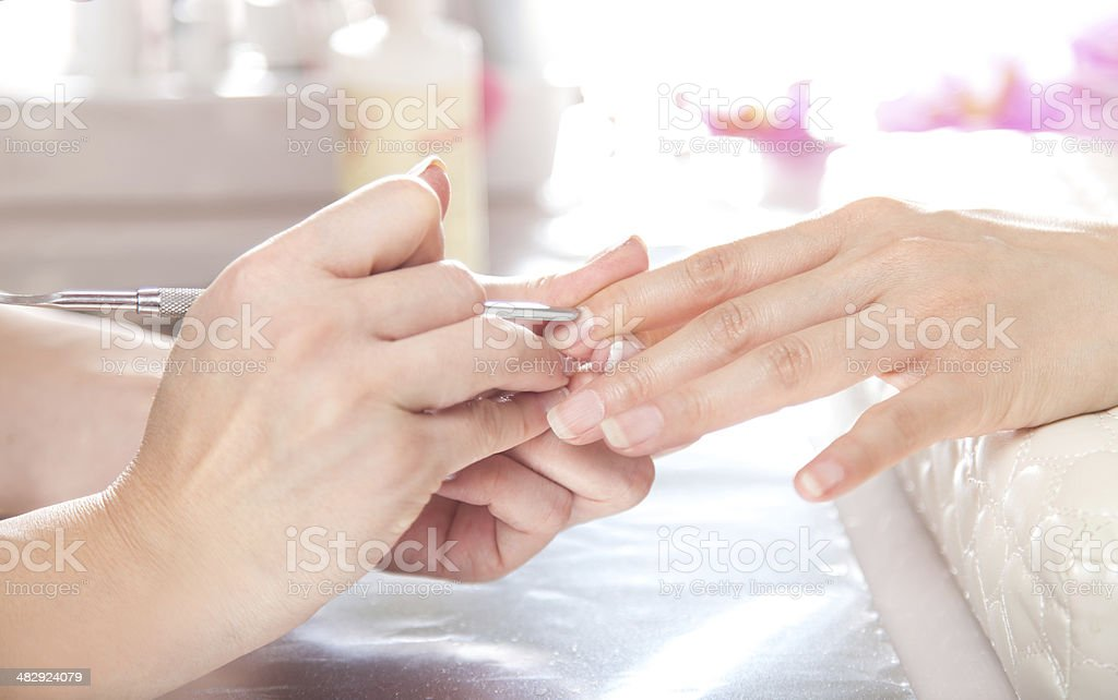 Nail salon. cuticles care with cuticle pusher. stock photo