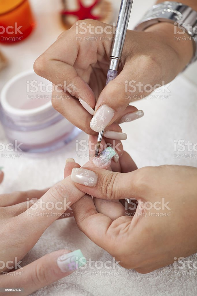 Nail technician applying varnish with a paintbrush royalty-free stock photo