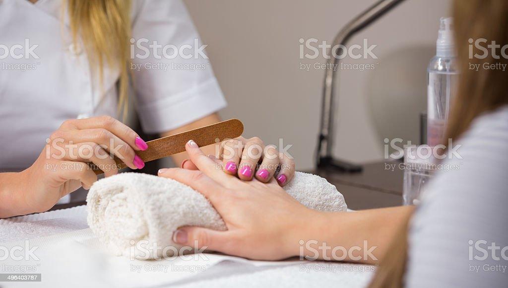 Nail technician filing customers nails at the nail salon
