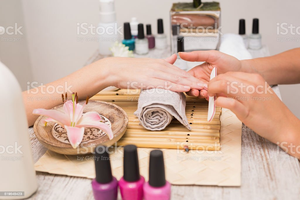 Nail technician giving customer a manicure stock photo