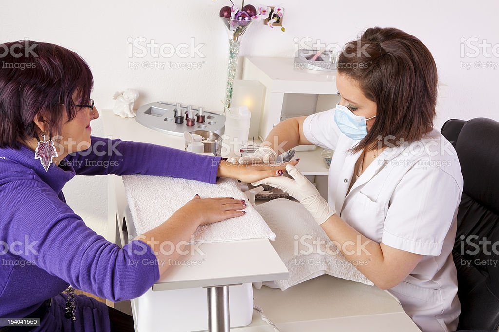 Nail technician giving manicure to woman stock photo