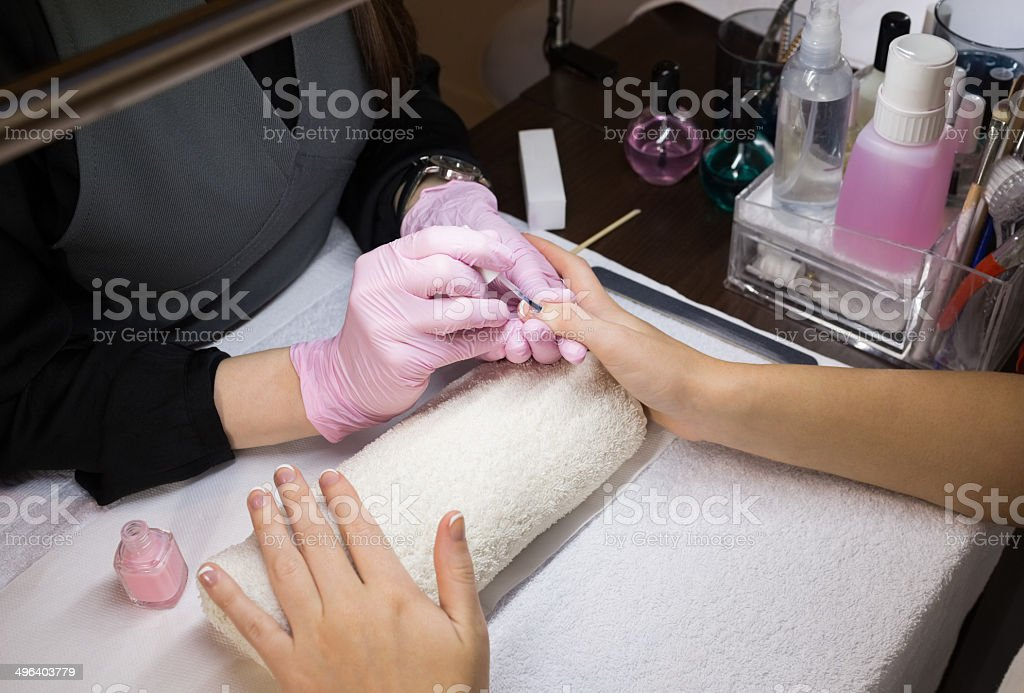 Nail technician in pink gloves painting customers nails at the nail...