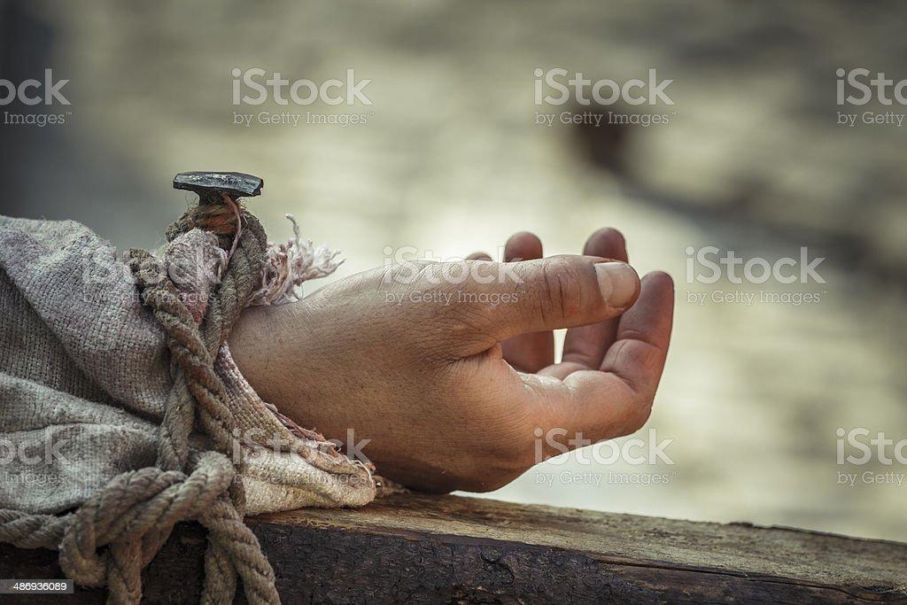 Nailed hand on cross stock photo