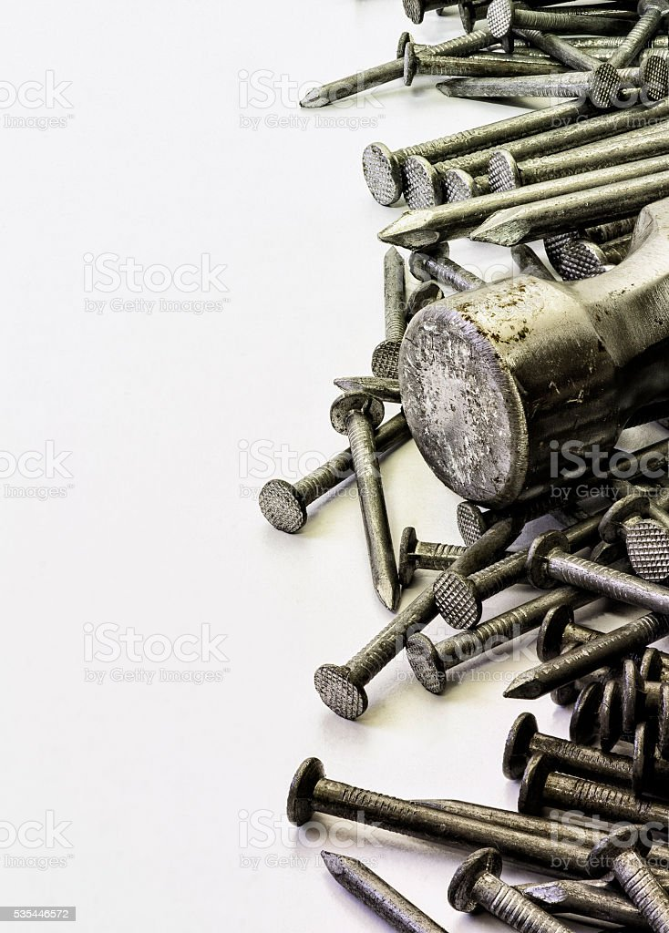 Nails and hammer on white background. stock photo