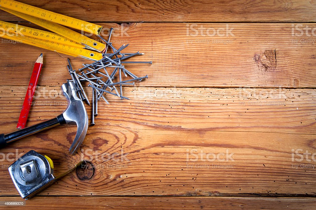 Nails, hammer, roulette, pencil and folding ruler on wooden background stock photo
