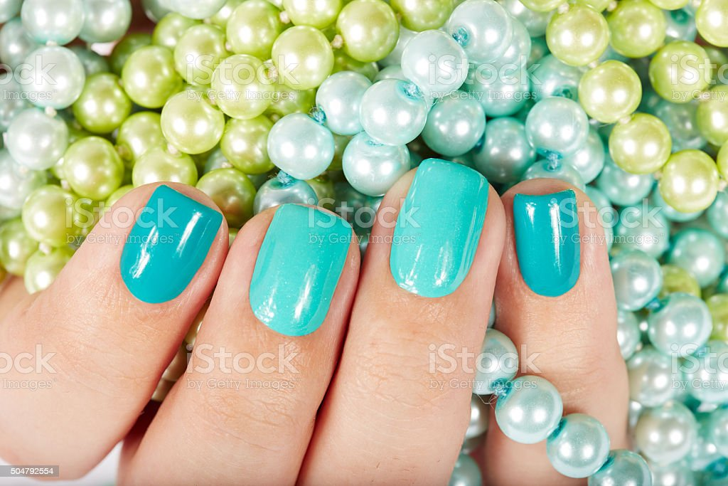 Nails with manicure on colored pearls background stock photo