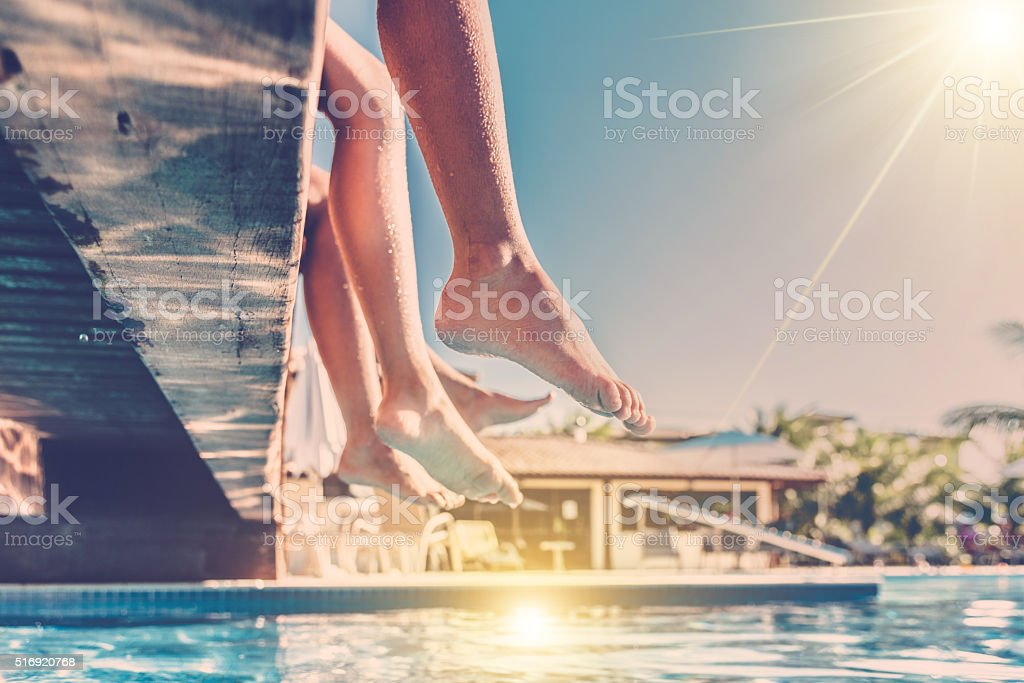 naked legs dangling  over blue swimming pool stock photo