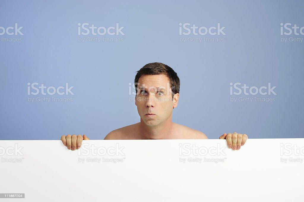 Naked man hiding behind white card royalty-free stock photo