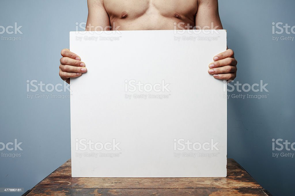 Naked man holding a white board royalty-free stock photo