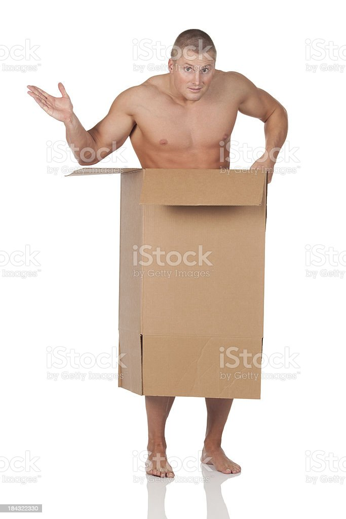 Naked man standing in a cardboard box royalty-free stock photo