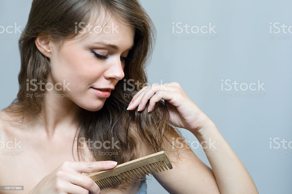 Naked woman combing her long hair with a comb  stock photo