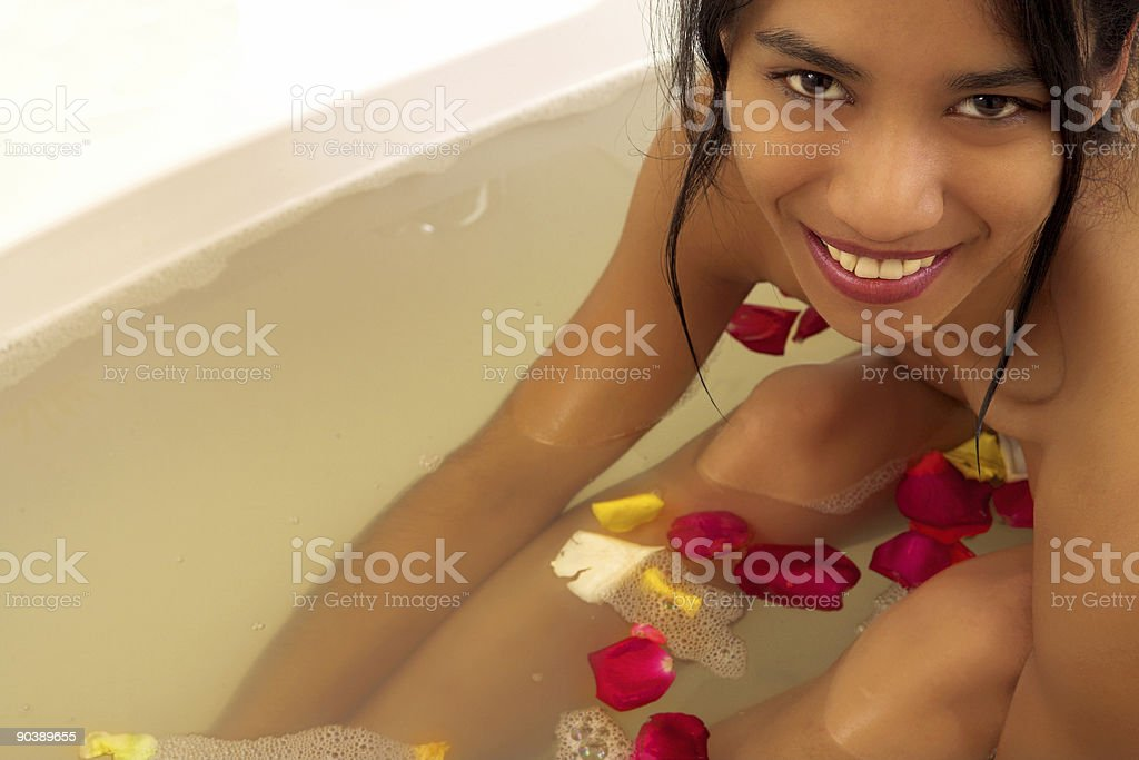 Naked woman in bath with rose petals royalty-free stock photo