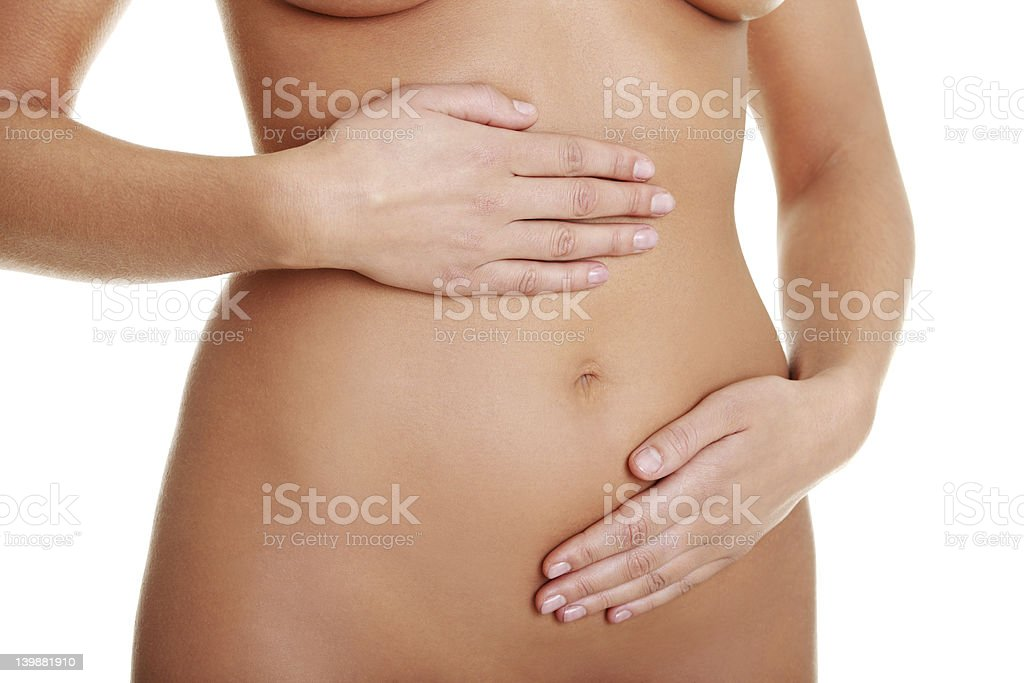 Naked woman with her hands on her abdomen stock photo