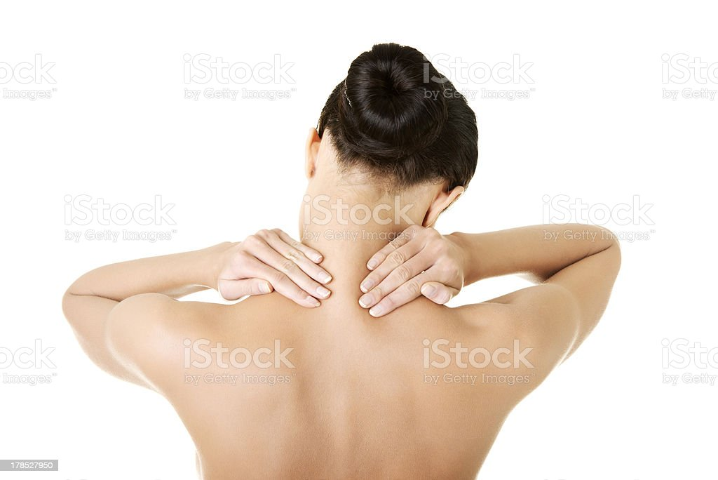 Naked young woman holding hands on neck in back pain. royalty-free stock photo