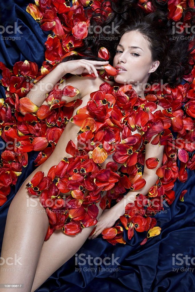 Naked Young Woman Laying with Tulip Petals All Over royalty-free stock photo
