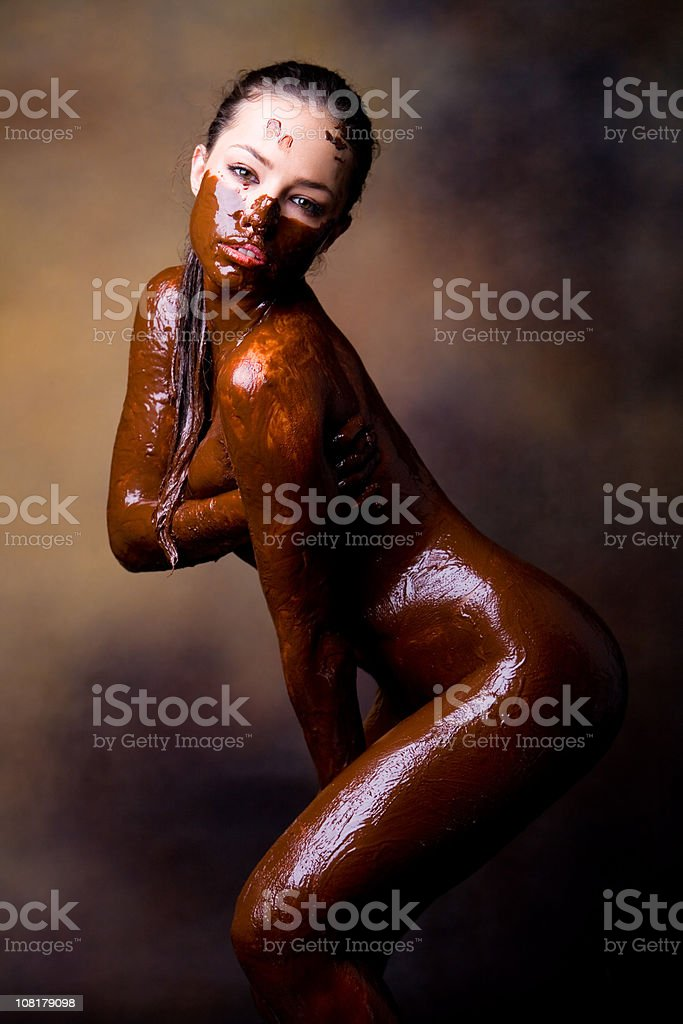 Naked Young Woman Posing and Covered in Melted Chocolate royalty-free stock photo