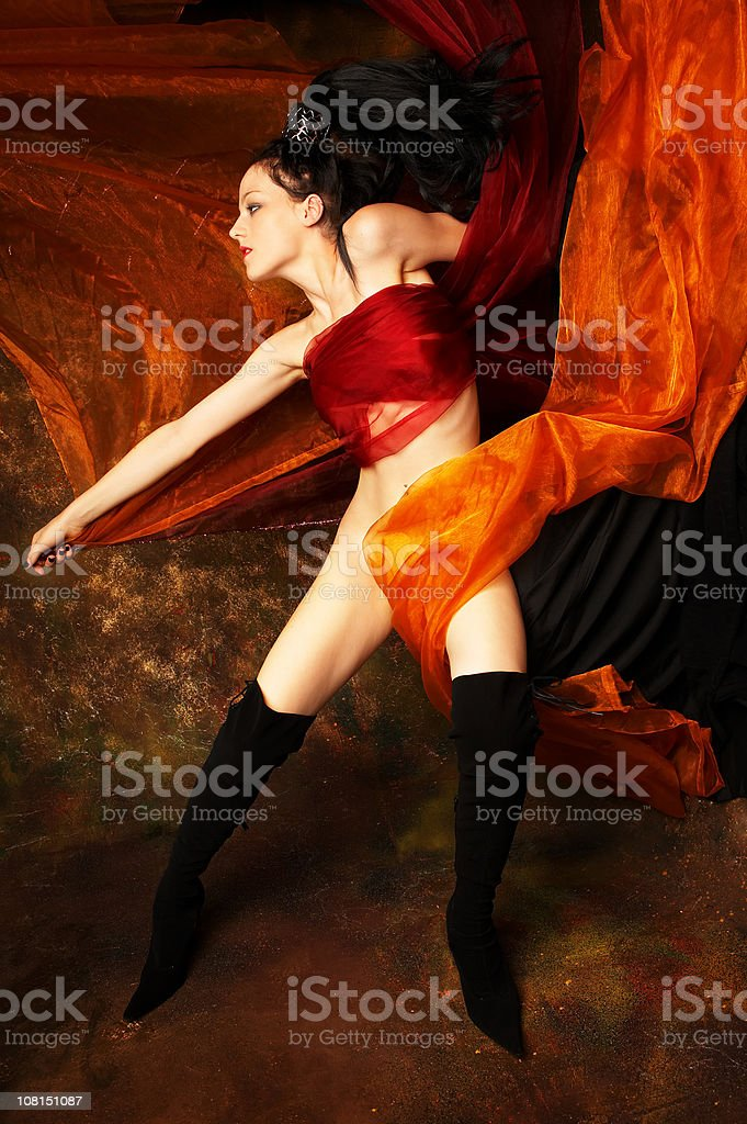 Naked Young Woman Posing and Wrapped in Orange Silk royalty-free stock photo