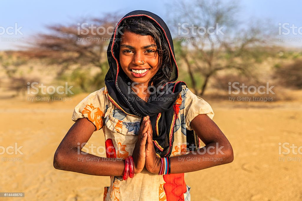 Namaste! Portrait of happy Indian girl in desert village, India stock photo