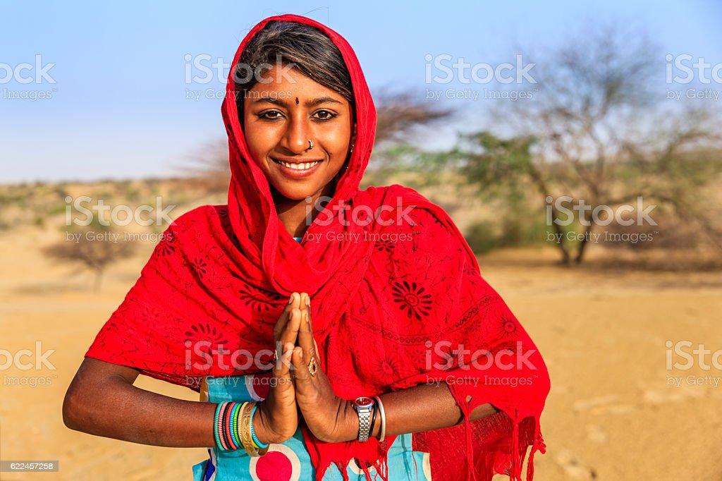 Namaste! Portrait of happy Indian girl in desert village, India stock photo