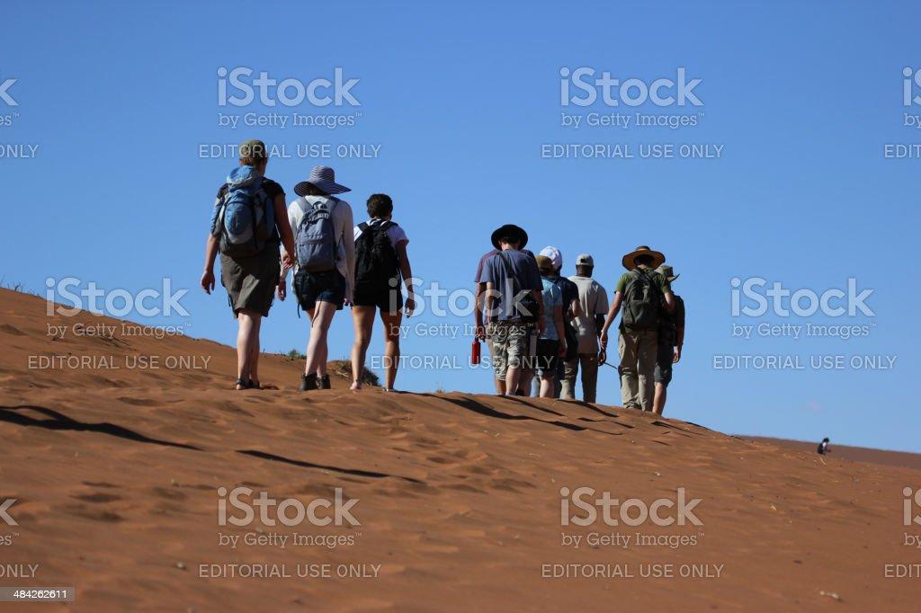 Namibia: Tourists climbing a sand dune in the Namib Desert stock photo