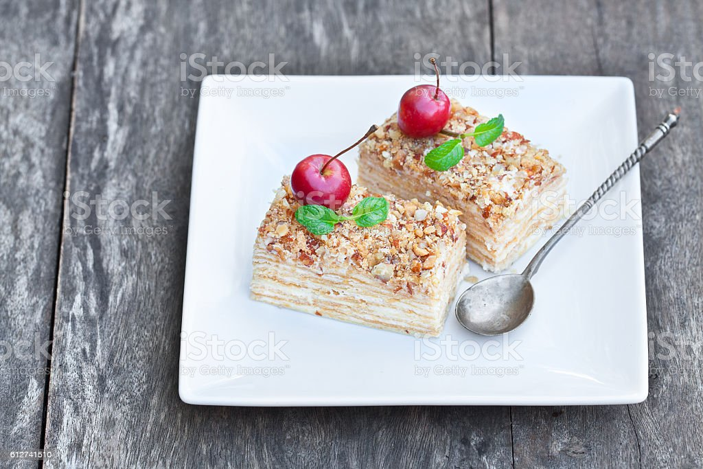 Napoleon  cake with wild apples and mint on squared plate stock photo