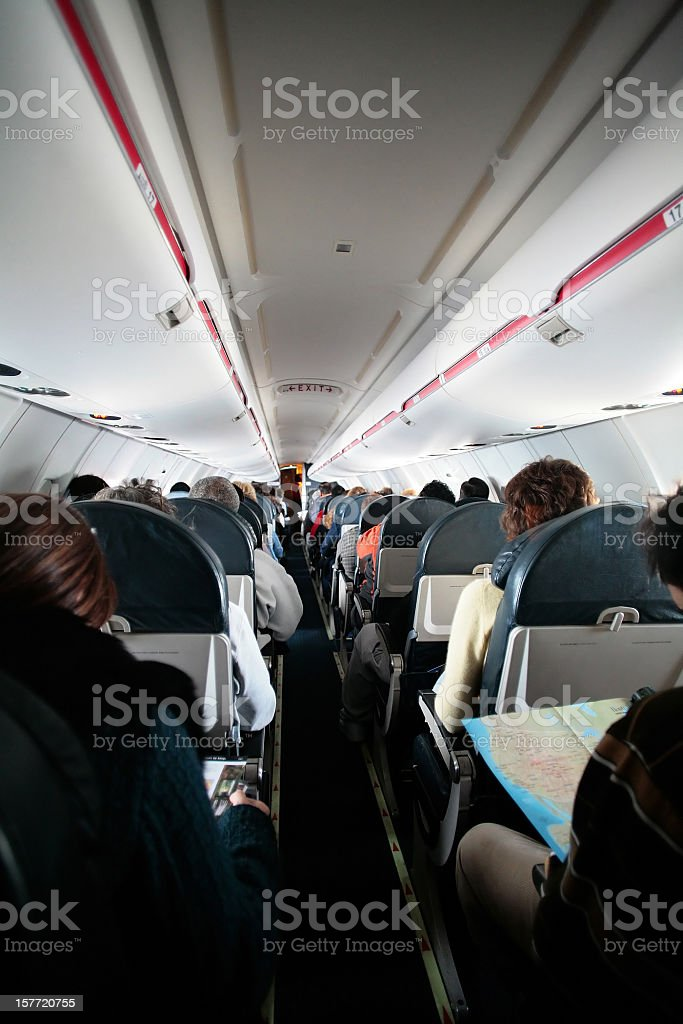 Narrow aisle in an airplane with passengers stock photo