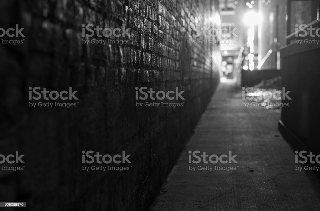 narrow defocused dark alleyway in black and white stock photo