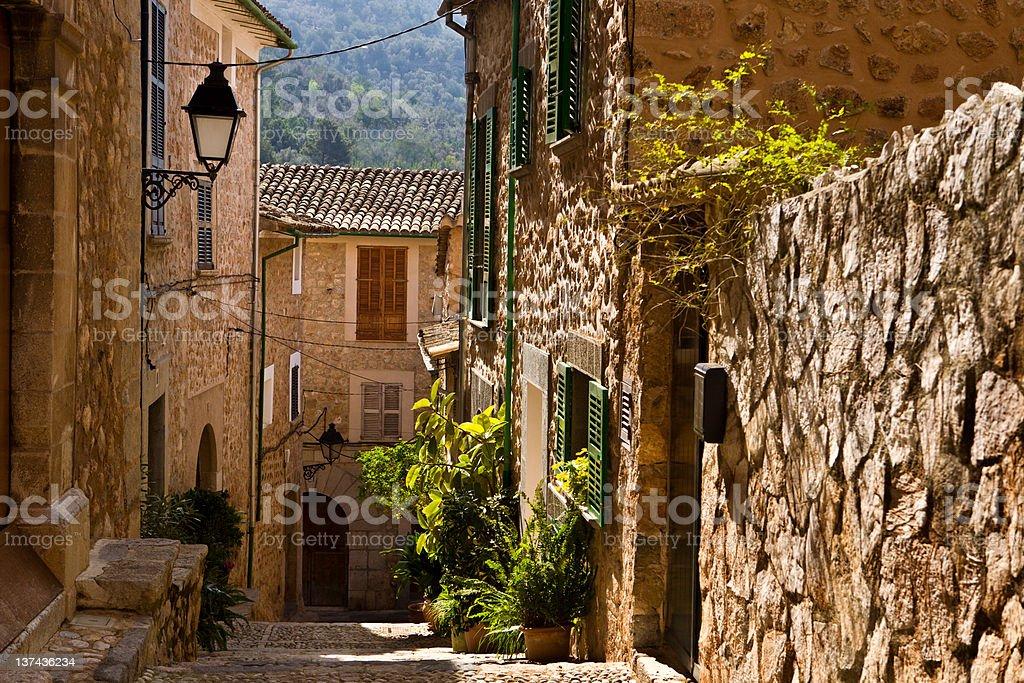 Narrow Spanish village street in between stone houses royalty-free stock photo