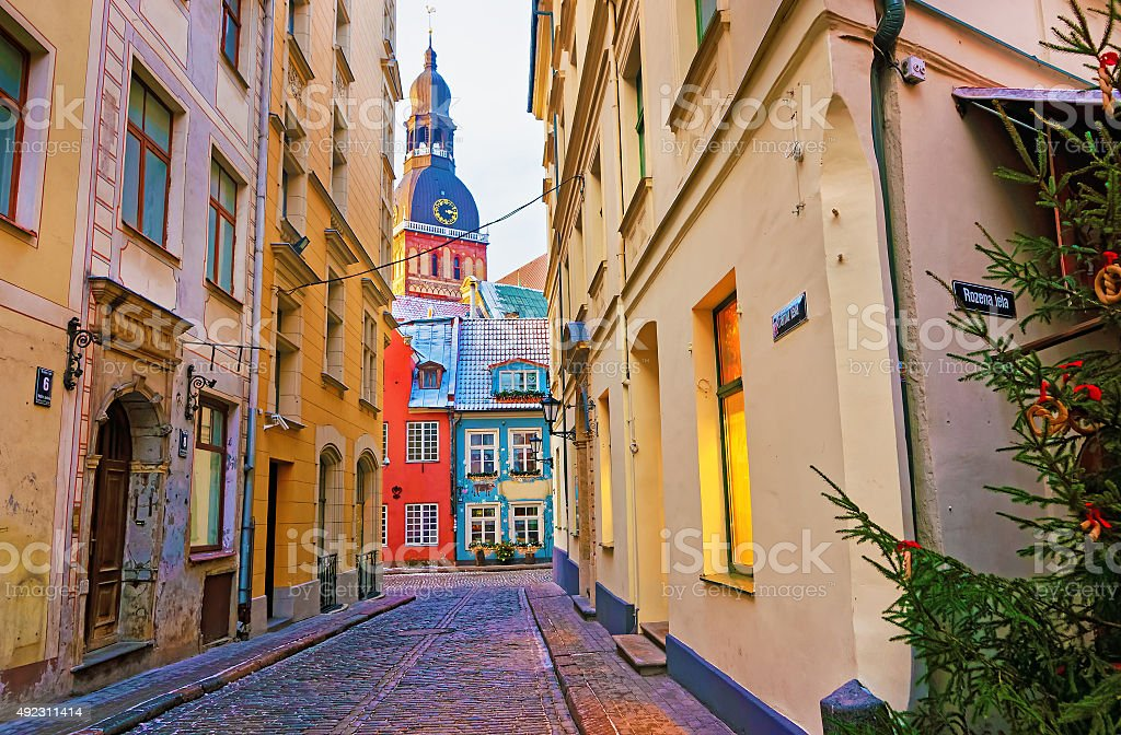 Narrow street leading to St. Peter church in Old Riga stock photo