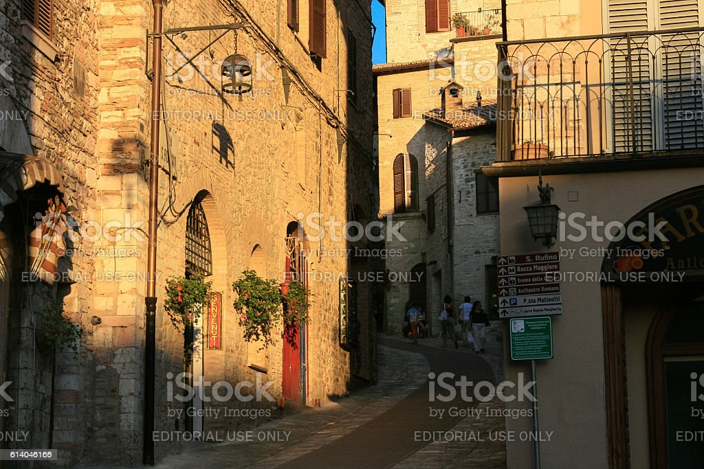 Narrow Street, Stone Buildings and Tourists at Sunset, Assisi, Italy. stock photo