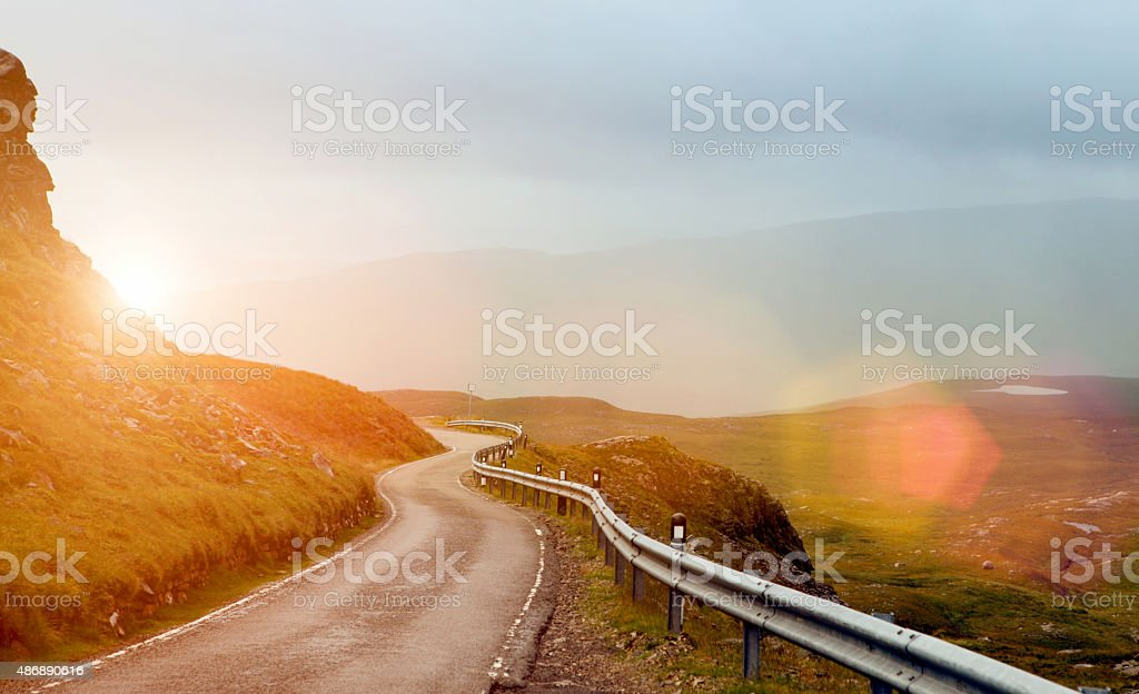 Narrow winding road in a valley at sunset stock photo