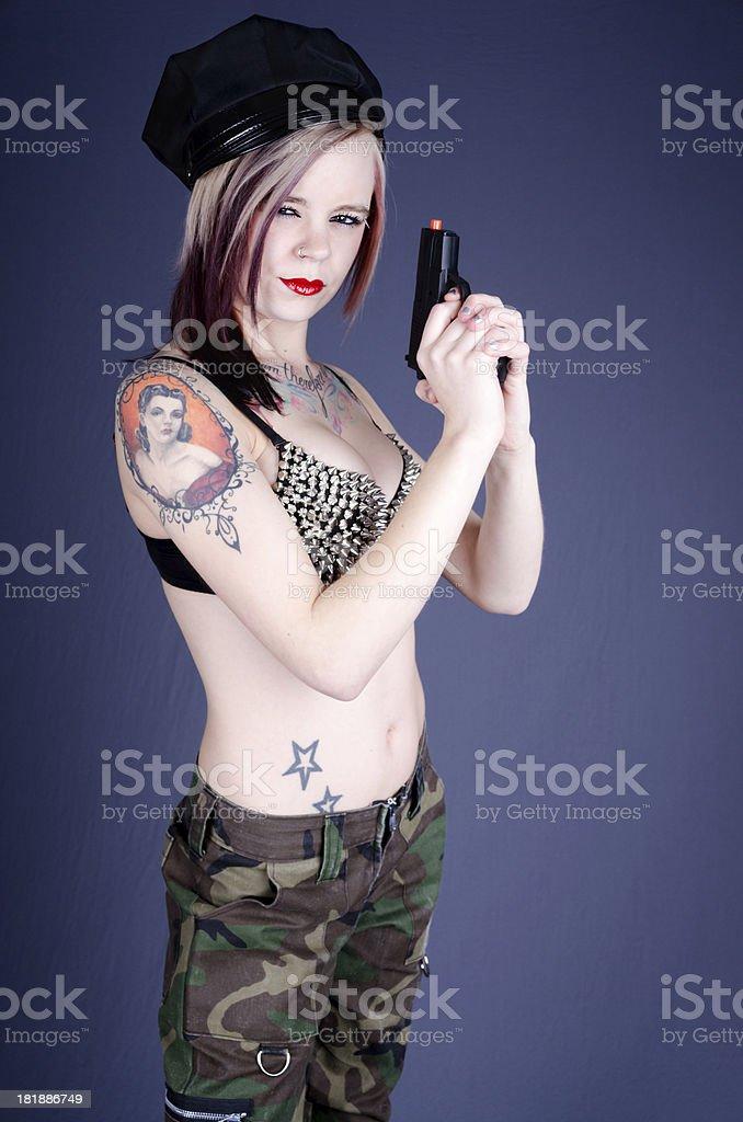 Narrow-eyed tattooed woman holding toy gun. stock photo