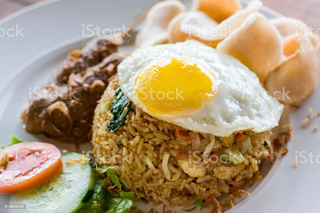 Nasi Goreng indonesian fried-rice dish with egg and chicken satay stock photo