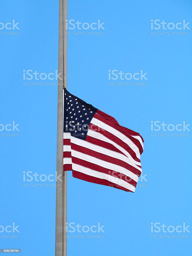 USA National Flag Flying Half Mast Blue Sky Memorial Remembrance stock photo
