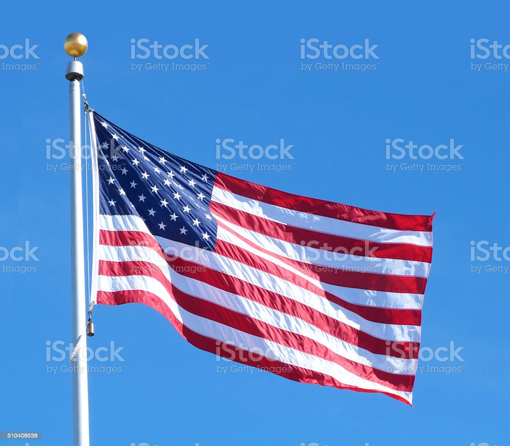 USA National Flag Flying Pole Blue Sky Stars Stripes Patriotism stock photo