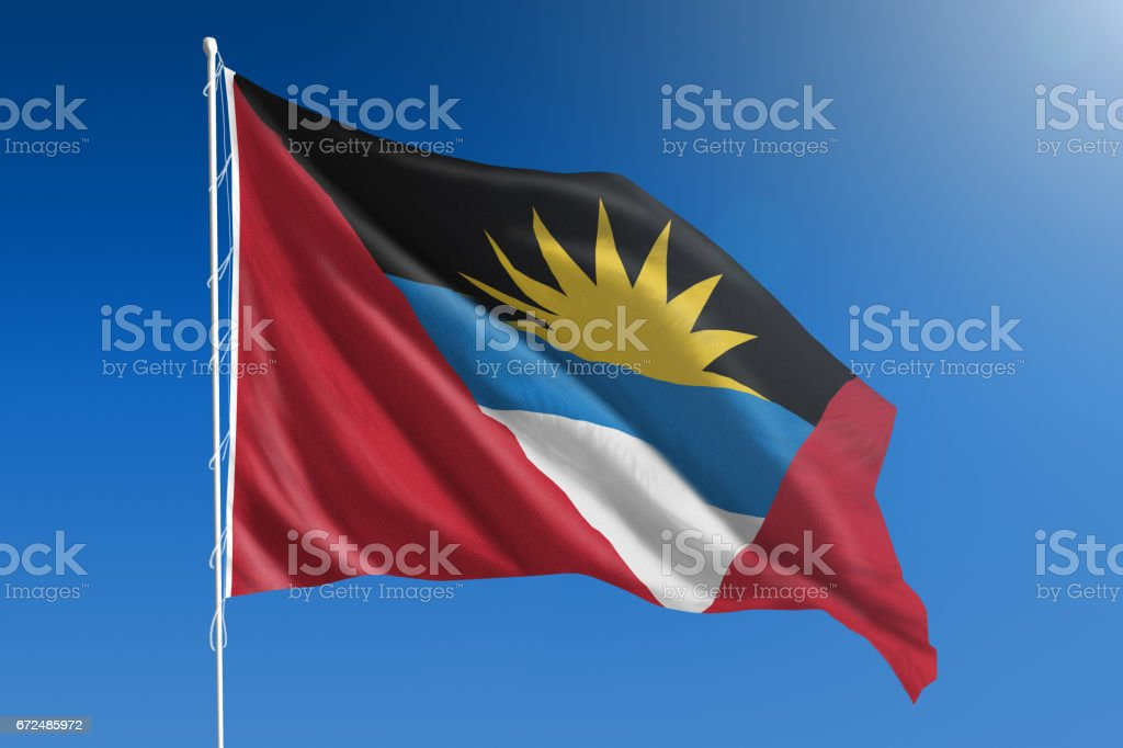 National flag of Antigua and Barbuda on clear blue sky stock photo