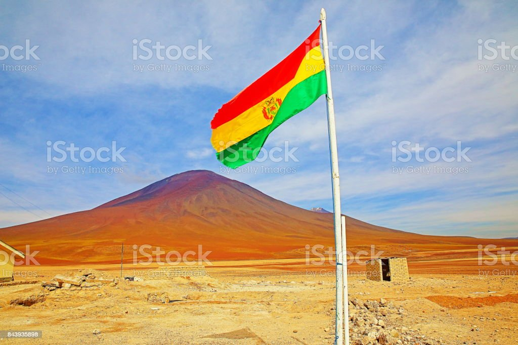 National flag of Bolívia waving on Bolivian Andes altiplano at sunrise and volcanoes near Uyuni, Idyllic Atacama Desert, snowcapped Volcanic steppe puna landscape panorama – Potosi region, Bolivian Andes, Chile, Bolívia and Argentina border stock photo