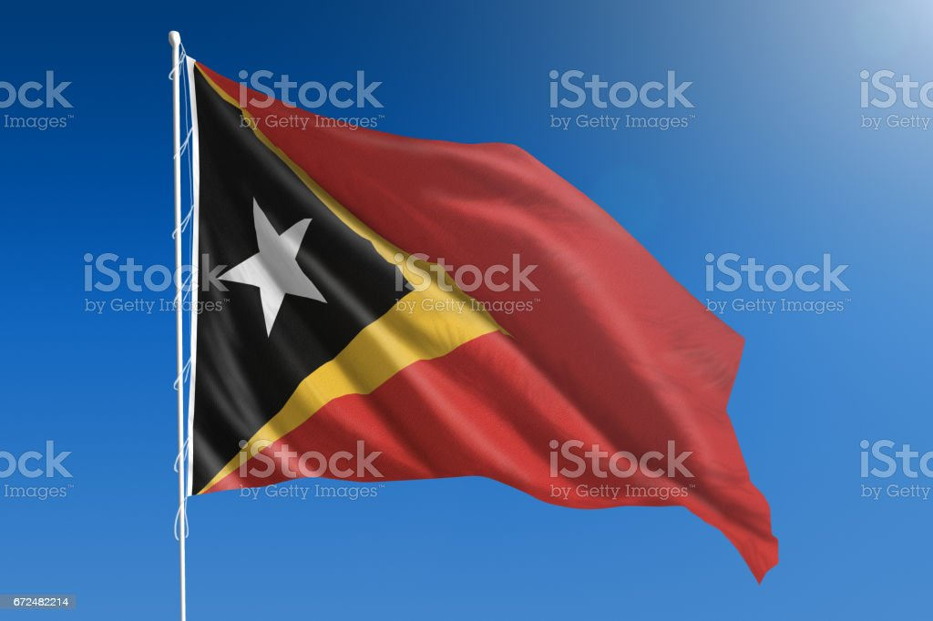 National flag of East Timor on clear blue sky stock photo