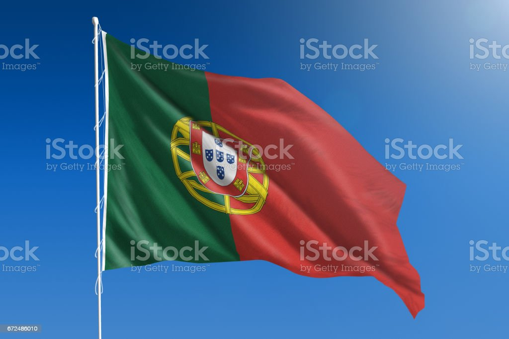 National flag of Portugal on clear blue sky stock photo