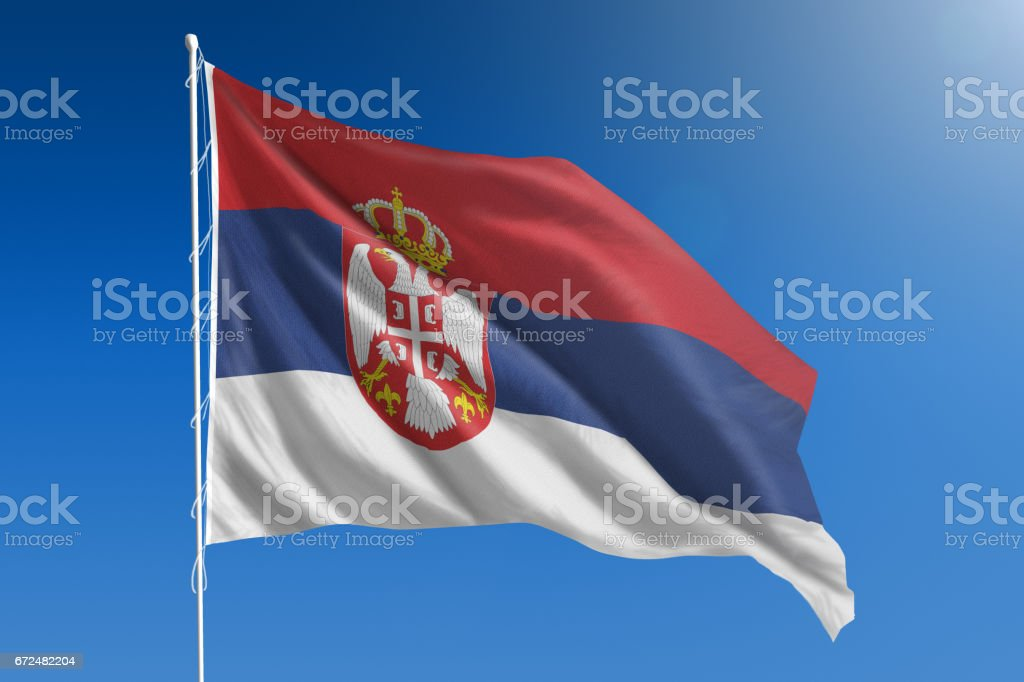 National flag of Serbia on clear blue sky stock photo