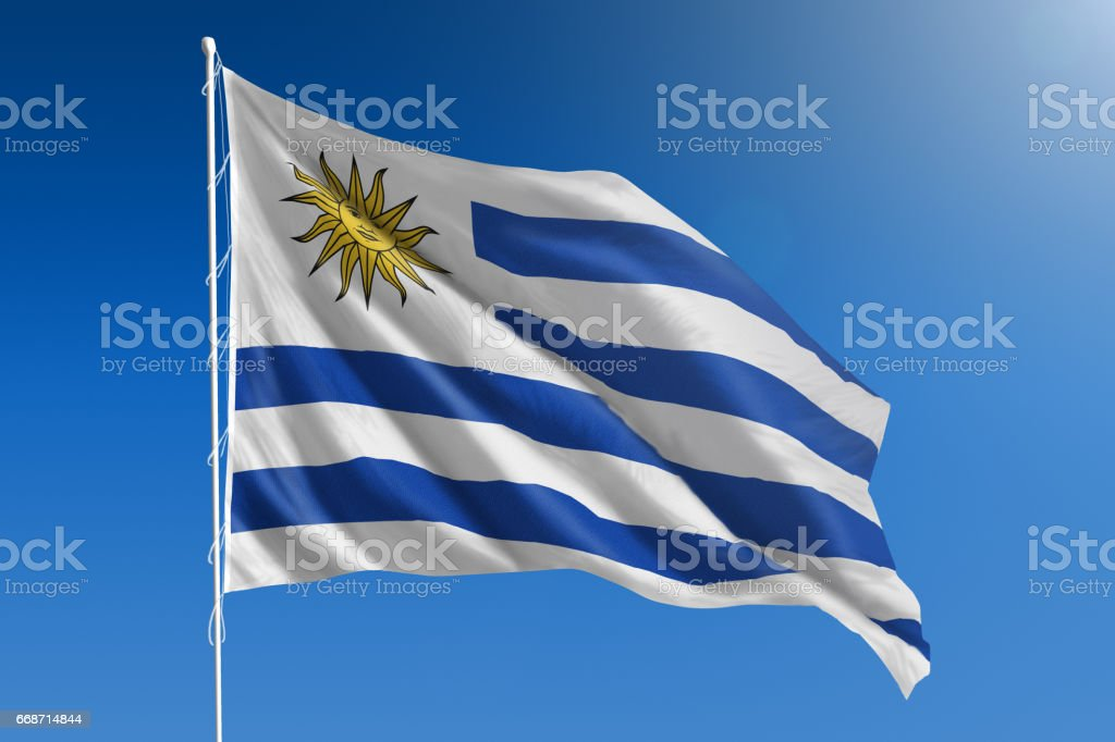 National flag of Uruguay on clear blue sky stock photo