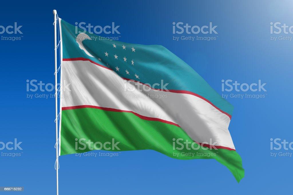 National flag of Uzbekistan on clear blue sky stock photo