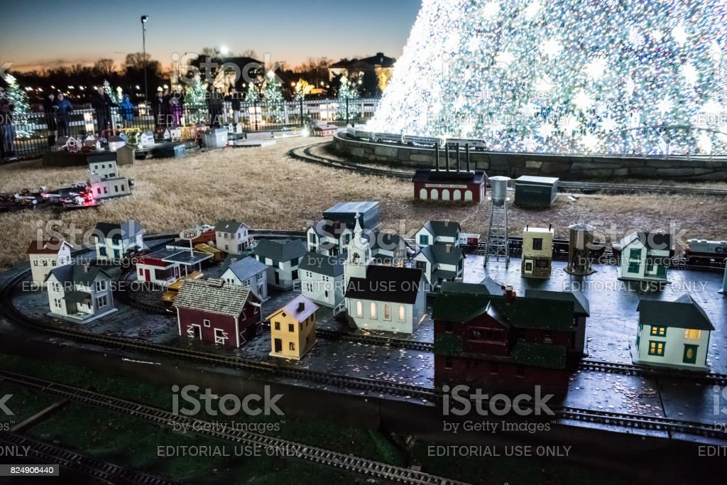 National Mall Christmas tree with visitors illuminated with toy trains and houses stock photo