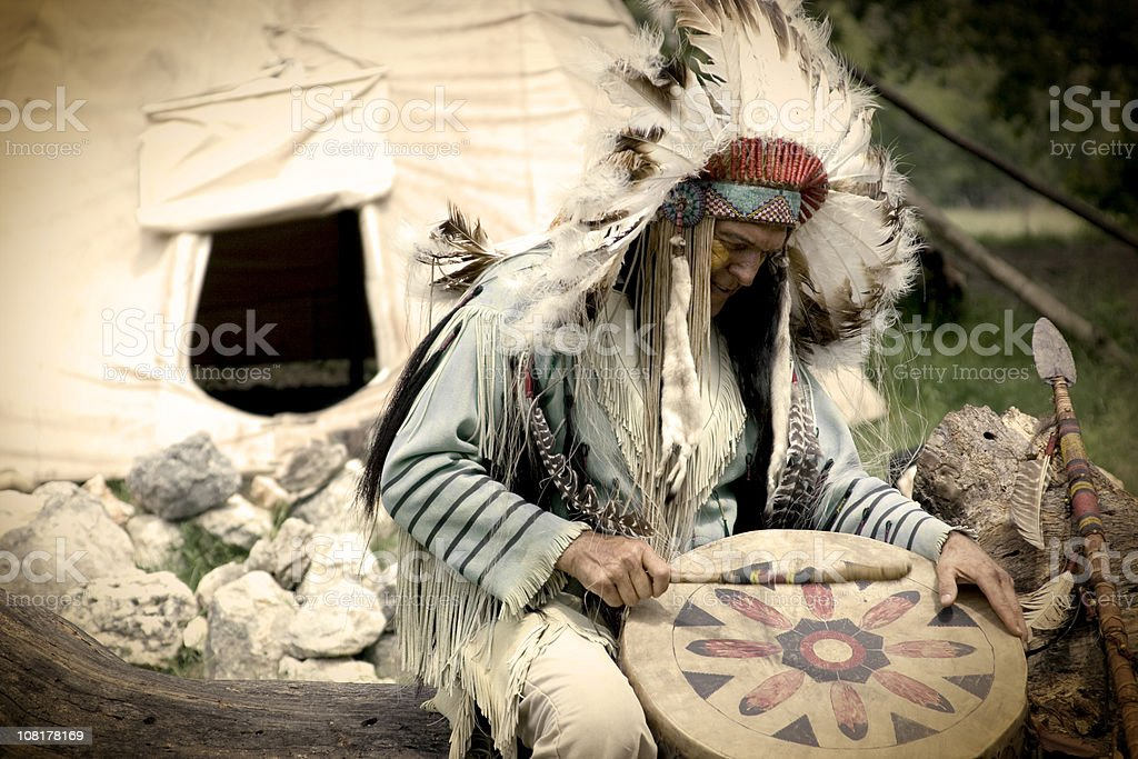 Native American Chief Playing Drum Outside Teepee stock photo