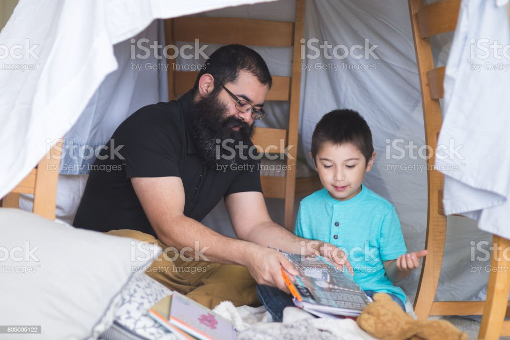 Native American dad reads with his young son under makeshift fort in living room stock photo